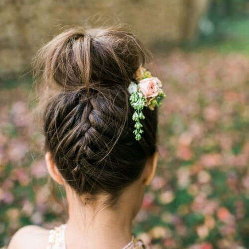 Decorate a French braid + bun combo with floral accent pieces flower girl hairstyles