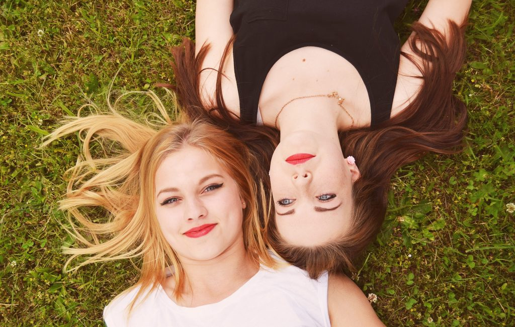 Two girls laying in the grass, one with blonde hair and one with brown hair from madison reed