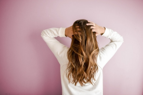 woman with hands in balayage hair