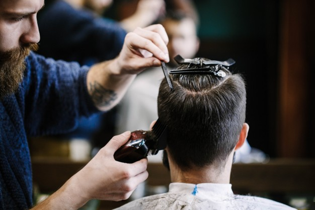 barber cuts man's hair with clipper brush
