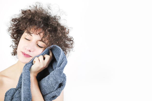 young woman wipes her face with towel