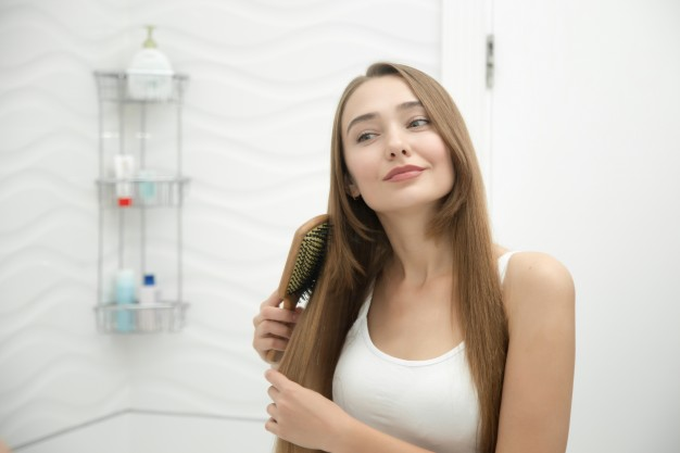 young woman smiling while combing her hair
